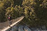 Man Crossing Footbridge, Matukituki River, Mount Aspiring National Park, Otago, Wanaka, New Zealand
