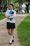 Young woman in school uniform, walking on path