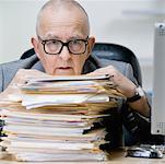 Senior man with stack of paperwork