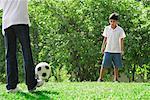 Un père et son fils jouent au foot ensemble