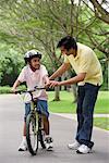 Un père enseigne à son fils à faire du vélo