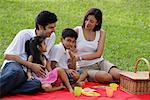 Une famille pique-niquer ensemble dans le parc