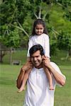 Un père porte sa fille sur ses épaules, car ils ont tous deux regardent la caméra