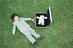 Petit garçon en costume complet, allongé sur l'herbe, à côté de la mallette ouverte contenant des ours en peluche
