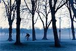 Cyclist Riding through Park, Edinburgh, Scotland