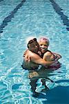 Embracing senior swimming couple in pool