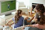 Famille dans le salon, regarder les sports à la télévision