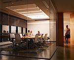 Three businesspeople in boardroom watching businessman leave