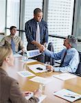 Zwei Geschäftsleute in Sitzungssaal Händeschütteln mit zwei Mitarbeiter beobachten