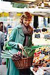 Femme portant le panier de légumes au marché