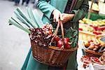 Femme portant panier plein de légumes