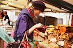 Femme payant au Stand de pain au marché en plein air