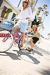 Frau Fahrradfahren, zieht Frau auf Skateboard, Newport Beach, Orange County, Kalifornien, USA
