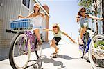 Frauen Reiten Fahrräder, zieht Frau auf Skateboard, Newport Beach, Orange County, Kalifornien, USA