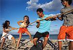 Friends Playing Tug-of-War on Beach