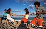 Amis de souque à la corde en jouant sur la plage