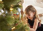 Mädchen sitzen am Weihnachtsbaum