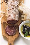 Italian salami, olives in olive oil, white bread