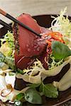 Filets de thon cru avec des graines de pavot sur salade dans un bol