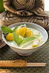 Soupe de noix de coco avec poissons & aubergines Thaïs devant Bouddha