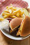 Cheeseburger, chips, mayonnaise, ketchup on plate