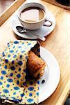 Une tasse de café avec un croissant au chocolat sur un plateau