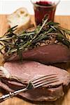 Rôti d'agneau au romarin, tranches taillées, pain blanc, vin rouge