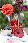 Petits fruits frais et fleurs sur la table rustique