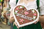 Woman in national dress holding Lebkuchen heart at Oktoberfest