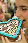 Woman biting into Lebkuchen heart at Oktoberfest
