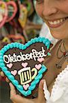 Woman holding Lebkuchen heart, a bite taken, at Oktoberfest