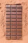A bar of dark chocolate on cocoa powder