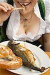 Femme mange Steckerlfisch & bretzel (fête de la bière, Munich)