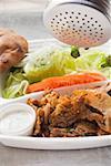 Sprinkling seasoning on döner kebab in lunch tray