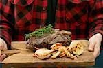 Man serving grilled T-bone steak on chopping board
