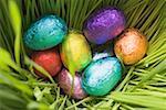 Oeufs en chocolat, emballées dans du papier de couleur, dans l'herbe (gros plan)
