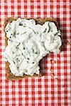 Quark & ramsons on wholemeal bread, a bite taken (overhead)