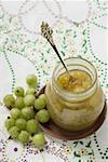 Jar of gooseberry jam and fresh gooseberries