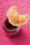 Croissant on a jar of raspberry jam (overhead view)