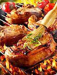 Brossage de côtelette de porc sur la grille du barbecue avec de l'huile