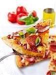 Slice of pepperoni pizza on server
