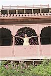 Woman throwing flowers from balcony, Neemrana Fort Palace, Neemrana, Alwar, India