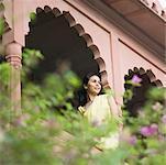 Young woman sitting on the railing of a palace, Neemrana Fort Palace, Neemrana, Alwar, Rajasthan, India