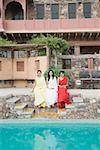Three young women sitting at the poolside, Neemrana Fort Palace, Neemrana, Alwar, Rajasthan, India
