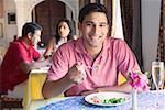 Porträt eines jungen Mannes in einem Restaurant zu sitzen und Lächeln