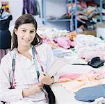 Portrait d'un créateur de mode féminin assis dans l'industrie textile et souriant