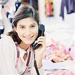 Portrait d'un créateur de mode femme parlant au téléphone et souriant
