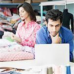 Gros plan d'un créateur de mode masculin à l'aide d'un ordinateur portable avec un créateur de mode féminin en arrière-plan