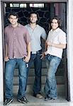 Portrait de trois jeunes hommes rassemblés et souriant
