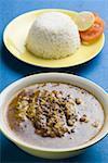 Erhöhte Ansicht einer Schale von Curry mit Reis und Salat auf einem Teller